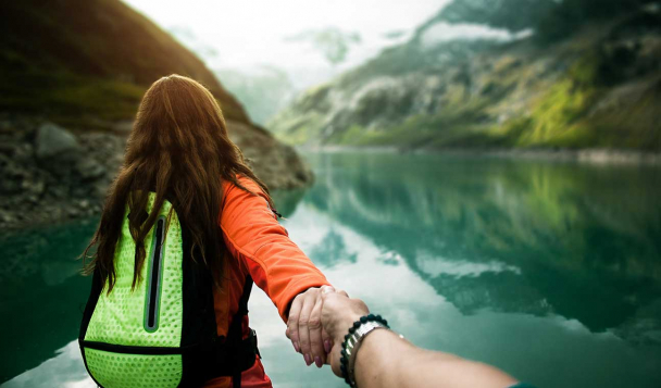 People holding hands and looking out toward a glacier lake with mountains surrounding it