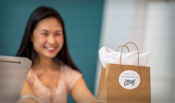 Smiling woman from a local community store offering a paper bag with thank you for supporting local
