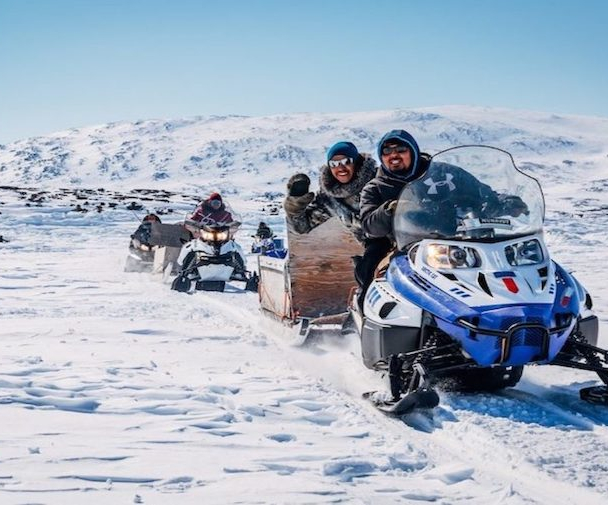 A group of people riding snowmobiles in northern Canada
