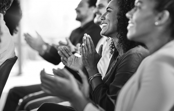 Close up of an audience smiling and applauding