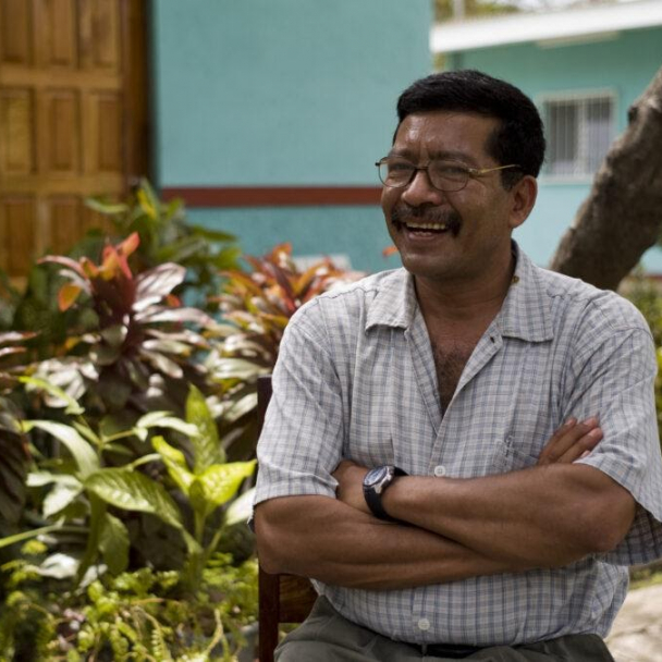 A Liberation Nuts farmer sat smiling in a green garden area